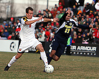 Jason Herrick #9 of the University of Maryland holds the ball away from Hamoody Saad #17 of the University of Michigan during an NCAA quarter-final match at Ludwig Field, University of Maryland, College Park, Maryland on December 4 2010.Michigan won 3-2 AET.