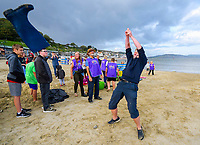 BNPS.co.uk (01202 558833)<br /> Pic: Graham Hunt/BNPS<br /> Date: 8th August 2021.<br /> <br /> Holidaymakers and locals compete in the over 12's section of the Welly Wanging competition on the beach at the seaside resort of Lyme Regis in Dorset during the towns Regatta and Carnival Week.  A competitor loses his grip sending the welly forward into the spectators.<br /> <br /> The aim of the Welly Wanging is to throw a boot full of water over your head as far as possible with each competitor getting three attempts.