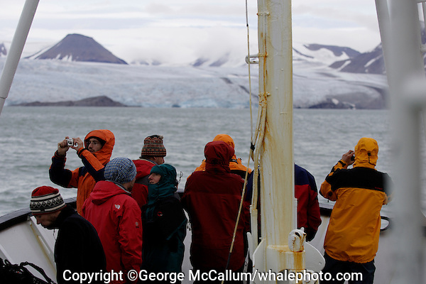 Ecotourists standing on ships bow approaching glacier in isfjorden on Spitzbergen Norway