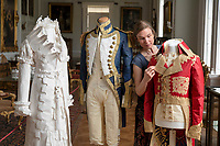 BNPS.co.uk (01202) 558833<br /> Pic: ZacharyCulpin/BNPS<br /> <br /> Pictured: Artist Stephanie Smart with the incredible paper outfits. (From left) A Regency 'walking dress' complete with a high necked spencer jacket, an early 19th century British naval uniform and a coat inspired by Napoleon.<br /> <br /> A textile artist has unveiled a collection of remarkable Regency outfits she has painstakingly made out of paper.<br /> <br /> Stephanie Smart has produced 11 life-sized outfits including a red frockcoat modelled on the style of Napoleon.<br /> <br /> Others depict walking dresses, naval uniforms and spencer jackets from the Regency era. (1795-1837)<br /> <br /> Her creations are on display as part of an exhibition titled The Regency Wardrobe at Firlie Place in East Sussex.
