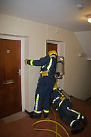 Firefighters wearing BA enter flat to rescue Male Adult. This image may only be used to portray the subject in a positive manner..©shoutpictures.com..john@shoutpictures.com