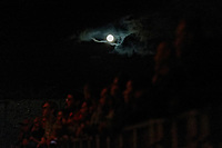 Pictured: The moon appears amongst clouds over the crowd at the Walled Garden stage. Saturday 21 August 2021<br /> Re: Green Man Festival near Crickhowell, Wales, UK.