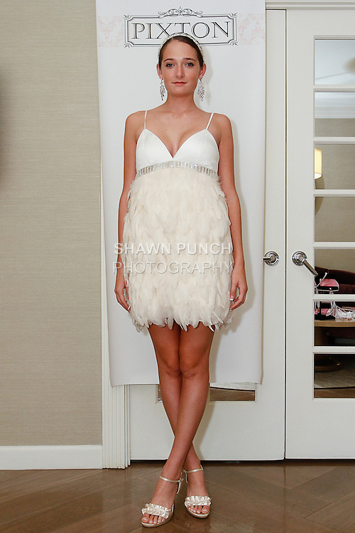 Model poses in a Charlotte wedding gown from the Pixton Couture Bridal Spring 2014 collection, by Kimberly Pixton Millar, during New York Bridal Market Week Spring 2014.