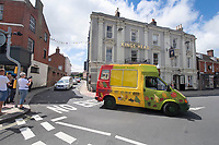 BNPS.co.uk (01202) 558833<br /> Pic: Zachary Culpin/BNPS<br /> <br /> Pictured: The convoy of ice-cream vans make their way through the town centre.<br /> <br /> A much-loved ice cream seller was given a fitting send off by colleagues who followed his funeral cortege in a convoy of 10 ice cream vans. <br /> <br /> John Lennie spent over 40 years selling ice creams from his trusty van in his local community.<br /> <br /> So dedicated was he to his job that he was still doing his rounds just two days before he died at the age of 79.<br /> <br /> His daughter, Jemma Lennie, led the procession in her father's old colourful truck at his funeral in Wimborne, Dorset.
