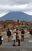 Pictured: Two Asian female tourists take a self portrait by  the ruins in Pompeii, as a thick dark cloud is forming over Mount Vesuvius in southern Italy. Thursday 27 February 2014