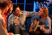 Smiling young couples socializing and playing the guitar.