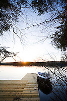 The sun sets over the lake directly opposite the location of the tree house on the opposite shore