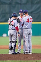 Hagerstown Suns pitching coach Sam Narron (43) has a chat on the mound with starting pitcher Lucas Giolito (27) and catcher Spencer Kieboom (20) during the game against the Greensboro Grasshoppers at NewBridge Bank Park on June 21, 2014 in Greensboro, North Carolina.  The Grasshoppers defeated the Suns 8-4. (Brian Westerholt/Four Seam Images)