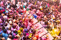 Holi devotee crowd at Banke Bihary Temple, believed birthplace of Krishna, receiving colored water from the priest, in Vrindavan, Uttar Pradesh India