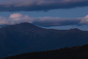 Mount Washington at night from Middle Sugarloaf Mountain in Bethlehem, New Hampshire USA during the summer months. The light on the righthand side of the ridge is from Lakes of the Clouds Hut.