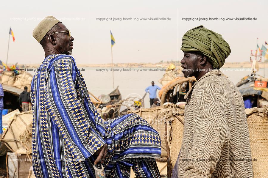 MALI, Mopti, river Niger, port with pinnace boats, market day, men with headgear, a coloured cloth called shesh or Tagelmust, the turban of Touareg, Haussa and Songhai / Mali, Mopti, Fluss Niger, Markttag und Warenhandel im Hafen mit Pinassen