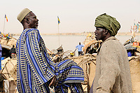 MALI, Mopti, river Niger, port with pinnace boats, market day, men with headgear, a coloured cloth called shesh or Tagelmust, the turban of Touareg, Haussa and Songhai / Mali, Mopti, Fluss Niger, Markttag und Warenhandel im Hafen mit Pinassen