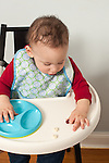 9 month old baby boy closeup in highchair wearing bib feeding self finger food pincer grasp picking up small piece of food