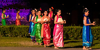 Beautiful Thai dancers carrying candles during Loy Krathong festival light show at Wat Mahathat Temple in the Sukhothai Historical Park, Thailand