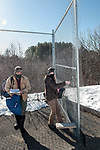 New Hampshire Fish and Game biological technician, Brett Ferry (L), and University of New Hampshire graduate student, Melissa Bauer (R) unlock and enter a 12 acre enclosure built for restoring a viable population of New England cottontail rabbits inside the Great Bay National Wildlife Refuge.