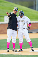 Wake Forest Demon Deacons head coach Tom Walter (16) talks to Nate Mondou (10) at third base during the game against the Duke Blue Devils at Wake Forest Baseball Park on April 25, 2014 in Winston-Salem, North Carolina.  The Blue Devils defeated the Demon Deacons 5-2.  (Brian Westerholt/Four Seam Images)