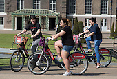Tourists using Santander Cycles bicycle hire scheme, Kensington Gardens, London.