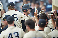 Jake Mueller (6) of the Wake Forest Demon Deacons is greeted by his teammates as he returns to the dugout after hitting a home run against the Virginia Cavaliers at David F. Couch Ballpark on May 19, 2018 in  Winston-Salem, North Carolina.  The Demon Deacons defeated the Cavaliers 18-12.  (Brian Westerholt/Four Seam Images)