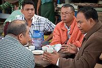 Myanmar, Burma.  Mandalay.  Burmese Men Talking in a Coffee Shop.