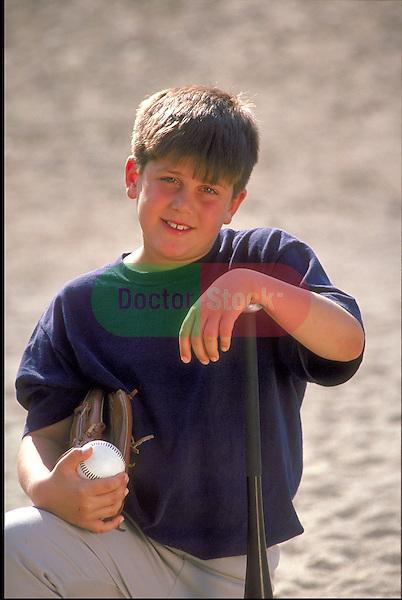 portrait of smiling boy holding baseball, baseball glove and baseball bat