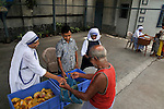 Nuns of Missionaries of Charity distributing food to local poor people at Prem dan - a home for physically and mentally challenged run by the missionaries of Charity, Kolkata, West Bengal, India. 21st August 2010. Arindam Mukherjee. Missionaries of Charity was founded by Mother Teresa