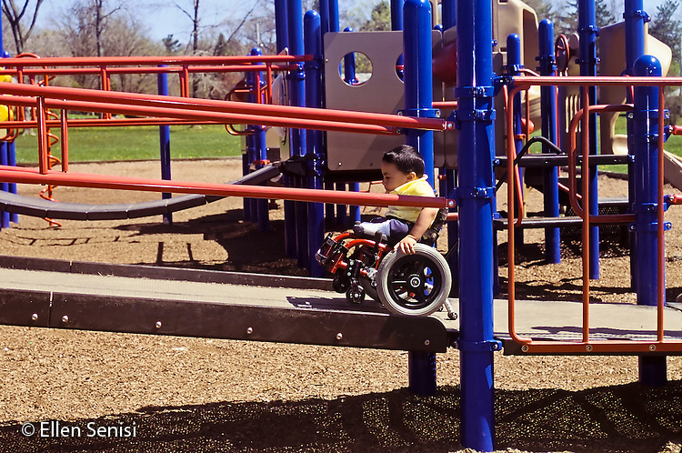MR / Schenectady, NY.Zoller Public School-Inclusion Class-Grade 1.Boy (7, Bangledeshi and Puerto-Rican-American, spina bifida, sacral agenesis) pushes himself up ramp on play equiptment on school playground..MR:  Rah1 .PN#: 29398                      FC#: 21675-00202.scan from slide.© Ellen B. Senisi