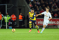 Sunday 09 November 2014 <br /> Pictured L-R: Alex Oxlade-Chamberlain of Arsenal against Tom Carroll of Swansea<br /> Re: Barclays Premier League, Swansea City FC v Arsenal City at the Liberty Stadium, Swansea, Great Britain.