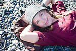 A beautiful blond young woman wearing a stylish hat lies on the beach along Dallas Road in Victoria, BC, British Columbia, Canada.