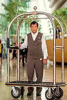 Porter Edward Chia, 63, in the lobby of the Marina Bay Sands resort hotel. He had to find a job after he retired, because his pension was not nearly enough for a decent living.