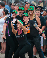Aug 18, 2018; Brainerd, MN, USA; NHRA pro stock motorcycle rider Angie Smith (front) takes a selfie with husband Matt Smith and crew during qualifying for the Lucas Oil Nationals at Brainerd International Raceway. Mandatory Credit: Mark J. Rebilas-USA TODAY Sports