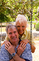 Retired senior couple having fun together at playground on swing