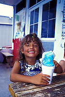 A young girl ( age 7 ) enjoys eating Shave Ice; a tasty cool treat on a hot hawaiian day.