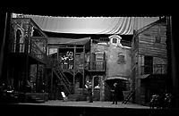 """23 février 1967. Plan d'ensemble de la scène et du décor principale de l'opéra """"Borgy and Bess"""". Quelques chanteurs sont placés dans différents endroits de la scène, sous la direction du metteur en scène ? Observation: Répétion, au Théâtre du Capitole de l'opéra américain """"Porgy and Bess"""", Musique de geoge Gershwin, à l'occasion du 30ème anniversaire de sa mort."""