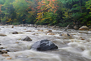 Autumn foliage along the East Branch of the Pemigewasset River in Lincoln, New Hampshire during the autumn months. This location is just above the site of the old 1900s Gravity Dam that was linked to the Lincoln Mill era.