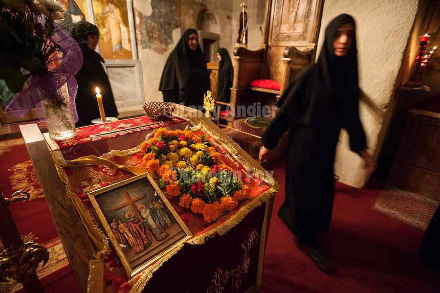 Nuns pass by the flower-enshrined icon of the Holy Cross at the conclusion of the Exaltation (Elevation) of the Holy Cross service, inside the Church of the Ascension of Jesus Christ at the Monastery Mileševa, Serbia originally built in the 13th century.
