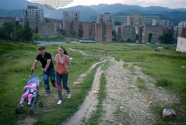 A couple with their baby in a pushchair climb a hill overlooking a housing estate in the town of Vulcan.