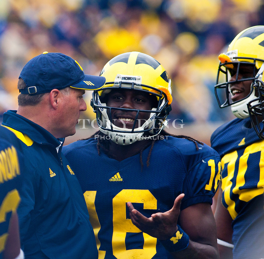 Michigan head coach Rich Rodriguez, left, talks with quarterback Denard Robinson (16) during a timeout in the fourth quarter of an NCAA college football game, Saturday, Sept. 4, 2010, in Ann Arbor. Michigan won 30-10. (AP Photo/Tony Ding)