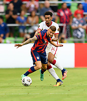 AUSTIN, TX - JULY 29: Paul Arriola #7 of the United States and Homam Ahmed #14 of Qatar battle for control of the ball during a game between Qatar and USMNT at Q2 Stadium on July 29, 2021 in Austin, Texas.
