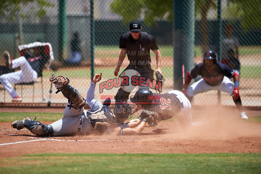 AZL Indians Red catcher Yainer Diaz (4) attempts to apply the tag as Ike Freeman (12) reaches to touch home plate during an Arizona League game against the AZL Indians Blue on July 7, 2019 at the Cleveland Indians Spring Training Complex in Goodyear, Arizona. Home plate umpire Bailey Dutten ruled Freeman out on the tag as Aaron Bracho (7) watches from the on deck position. The AZL Indians Blue defeated the AZL Indians Red 5-4. (Zachary Lucy/Four Seam Images)