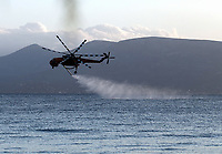 Pictured: A fire helicopter draws water from the sea nearby.<br /> Re: A forest fire has been raging in the area of Kalamos, 20 miles east of Athens in Greece. There have been power cuts, country houses burned and children camps evacuated from the area.
