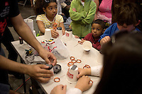 Children build small motors using magnets and copper wire in the Stata Center during the MIT Under the Dome open house in Cambridge, Massachusetts, USA.