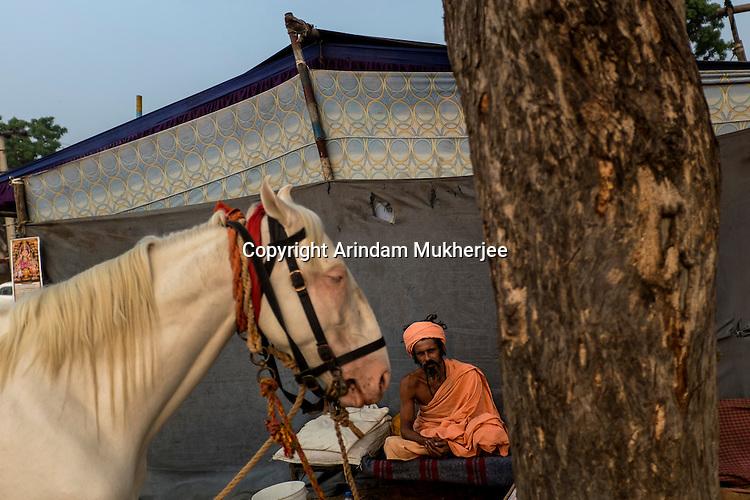Indian holy man sits on his cot at Pushkar fair ground. Rajasthan, India.