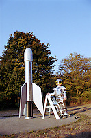 Boy (6-8) in space suit standing next to rocket