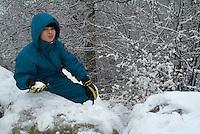 Nine year old boy climbing on snowy rocks, Selonnet, French Alps, France.
