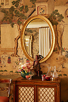 A gilt-framed, oval mirror hangs above an antique cabinet; the wall behind is hung with wallpaper with a Chinese scene motif. Glass decanters, flowers and a statuette are arranged on top of the cabinet.