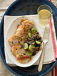 A plate of sliced roasted turkey breast and wild rice stuffing with green grapes, with a glass of white grape juice.