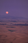 A pink full moon rises above the Palouse as seen from Steptoe Butte in Eastern Washington State.