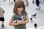 Venice Italy 2009. Young girl with feral pigeon in St Marks Square. Piazza San Marco.