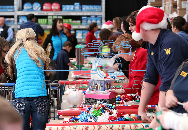 Volunteers wrap gifts at the 10th annual Holiday with a Hero event at Walmart in Carson City, Nev., on Wednesday, Dec. 17, 2014. The event pairs 200 of Carson City's K-5th grade homeless students with a local heroes for Christmas shopping. <br /> Photo by Cathleen Allison