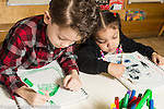 Education preschool 4 year olds boy and girl drawing side by side using opposite hands